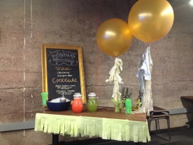 the drink station decorated with a handmade chalkboard, giant balloons, and fringe.